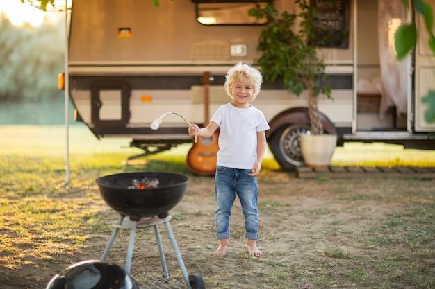 Ragazzo biondo che cucina caramella gommosa e molle al campeggio della famiglia