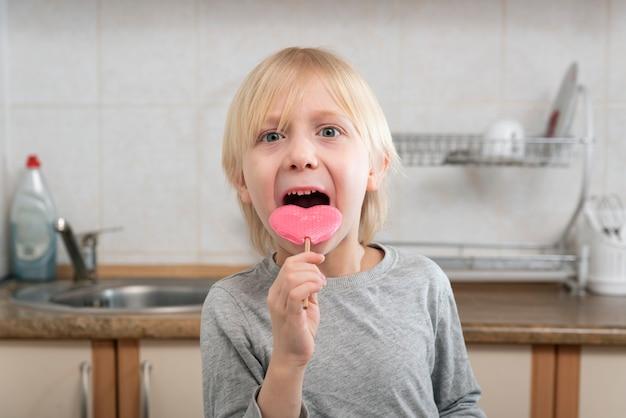Ragazzo biondo che mangia lecca-lecca rosa a forma di cuore