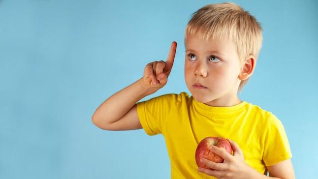 Il ragazzo biondo tiene in mano una mela e alza il dito pensieroso alza lo sguardo. nutrizione nei bambini.