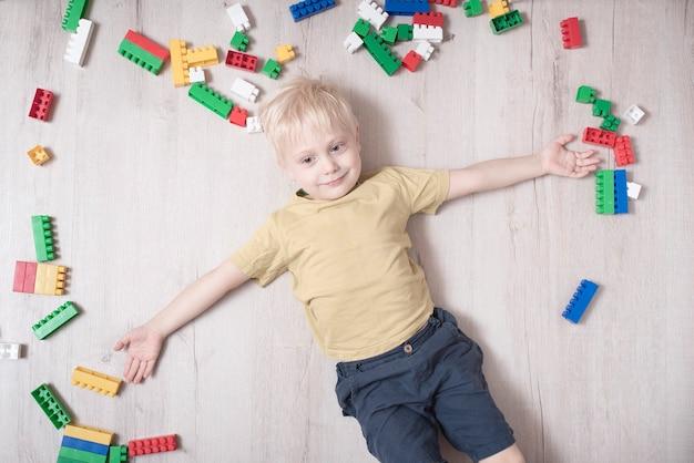 Il ragazzo biondo giace sul pavimento tra il designer. vista dall'alto