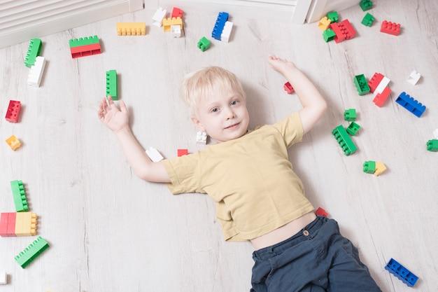Il ragazzo biondo si trova sul pavimento tra il designer. vista dall'alto