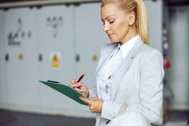 Bionda imprenditrice in piedi in un impianto di riscaldamento, tenendo appunti e controllando i macchinari.