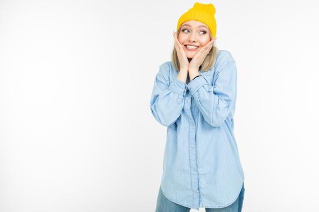 Affascinante ragazza bionda in un look casual con una camicia di jeans si abbraccia su uno sfondo bianco.