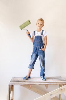 Un bambino biondo sta su una scala di costruzione e un rullo tra le mani