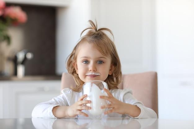 Biondo carino bambino con gli occhi azzurri con tracce di latte sulle labbra è in possesso di un bicchiere di latte ubicazione a un tavolo bianco in cucina