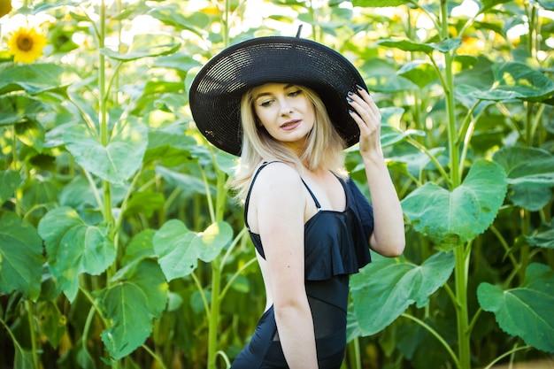 Ragazza bionda europea in costume da bagno nero e cappello sulla natura con girasoli