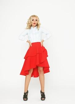 Modella bionda con capelli di lusso e gonna rossa in studio su sfondo bianco