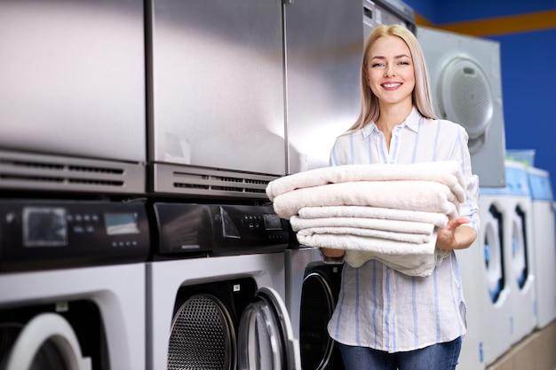 Femmina bionda sorridente felice facendo faccende in lavanderia, tenendo pila di asciugamani puliti freschi. molte lavatrici in sottofondo
