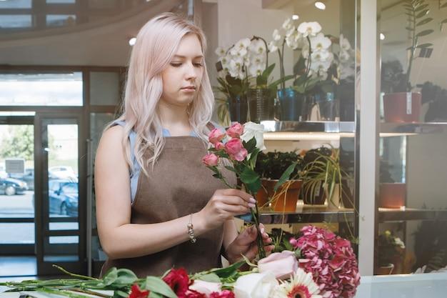 Donna bionda fiorista in grembiule nell'area di lavoro del negozio di fiori. messa a fuoco selettiva.