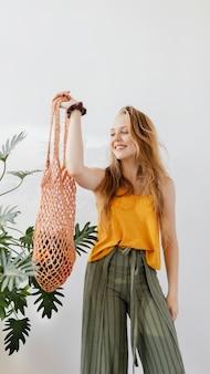 Ragazza bionda che tiene una borsa a rete con verdure all'interno della carta da parati del telefono cellulare