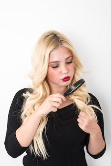 Ragazza bionda che si guarda i capelli con una lente d'ingrandimento su sfondo bianco