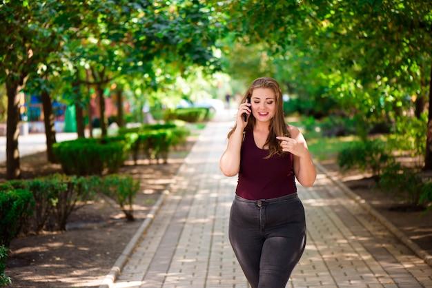 Modello di ragazza bionda plus nel parco. xxl girl.