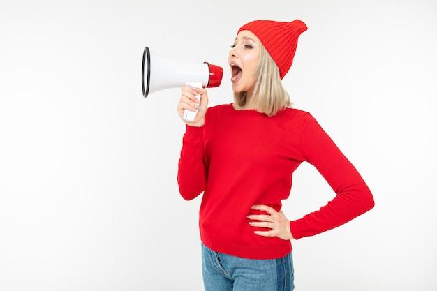 La ragazza bionda in vestiti rossi con un altoparlante in mani grida su un bianco