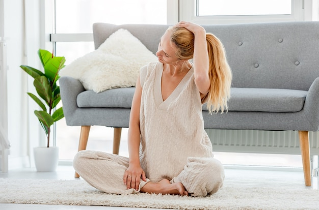 Ragazza bionda seduta sul pavimento e allungare il collo durante l'allenamento yoga mattutino a casa