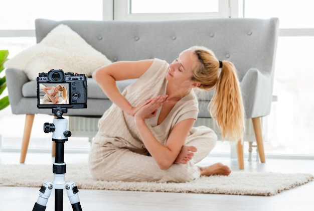 Ragazza bionda che si siede in asana yoga sul pavimento nella stanza con la luce solare