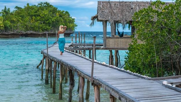 Ragazza bionda che soggiorna sul molo in legno di una famiglia cercando nell'oceano blu, gam island, papua occidentale, raja ampat, indonesia