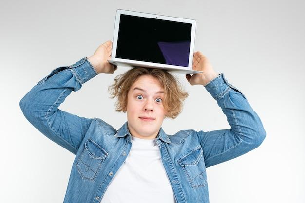 Il ragazzo biondo mostra uno schermo del computer portatile in un modello per l'inserimento di un sito web su una priorità bassa bianca