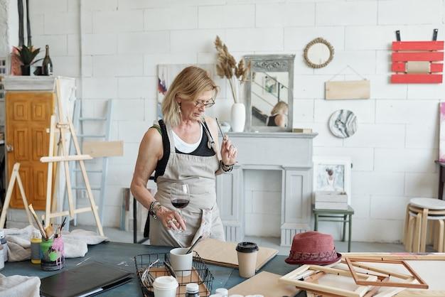 Artista dai capelli biondi in occhiali in piedi a tavola e bere vino mentre pensa a una nuova immagine