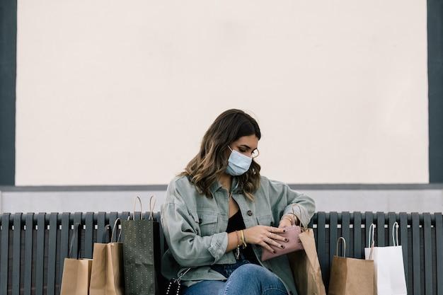 Donna bianca dai capelli biondi con maschera protettiva seduta su una panchina all'aperto circondata da sacchetti di carta della spesa guardando la sua borsa.