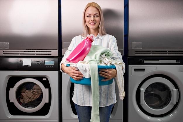 Donna bionda felice che tiene una bacinella di vestiti da lavare in una lavanderia automatica, giovane donna sta sorridendo alla telecamera, utilizzando un detersivo. lavaggio, pulizia, concetto di faccende domestiche