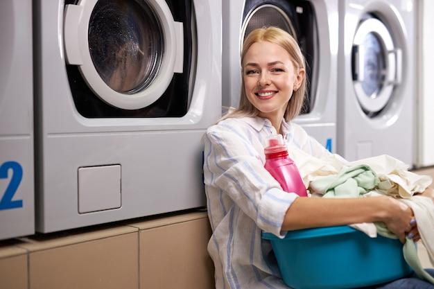 Donna bionda felice che tiene un cesto di vestiti da lavare in una lavanderia automatica, giovane donna si siede sul pavimento sorridendo alla telecamera. lavaggio, pulizia, concetto di faccende domestiche