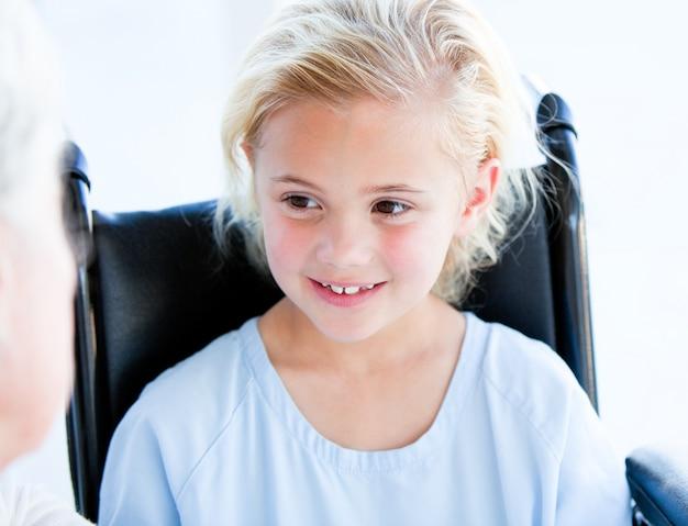 Bambina bionda che si siede su una sedia a rotelle