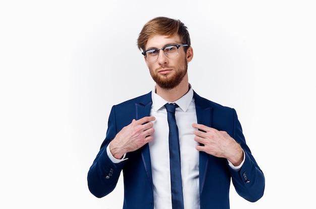 Un uomo biondo con gli occhiali e un completo classico si raddrizza la cravatta intorno al collo
