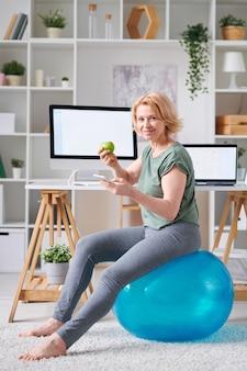 Donna matura bionda in abbigliamento sportivo che mangia mela verde fresca e lo scorrimento in smartphone mentre era seduto su fitball davanti al monitor del computer
