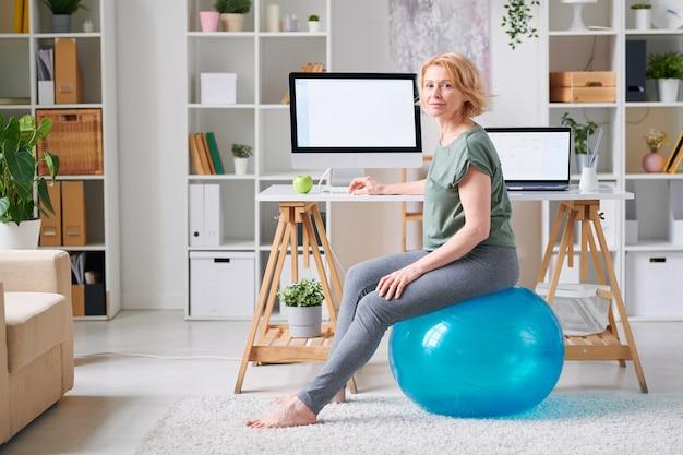 Donna matura bionda in abbigliamento sportivo seduto su fitball dalla scrivania davanti al monitor del computer mentre si va a fare esercizio a casa