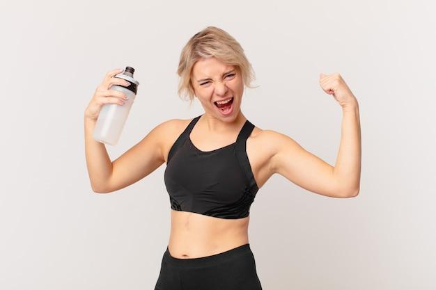Bella donna bionda in forma con una bottiglia d'acqua