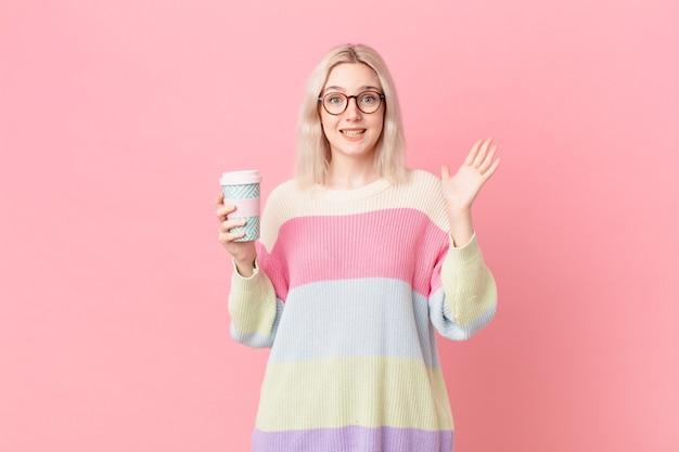 Bella donna bionda che si sente felice e stupita per qualcosa di incredibile. concetto di caffè