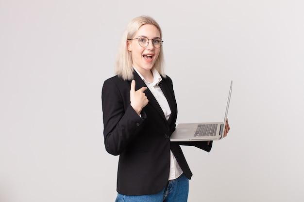 Bella donna bionda che si sente felice e indica se stessa con un eccitato e tiene in mano un laptop