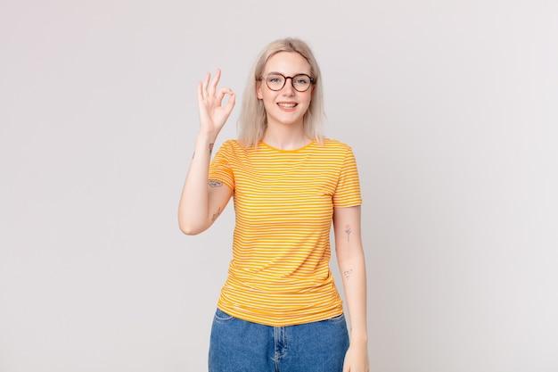 Bella donna bionda che si sente felice, mostra approvazione con un gesto ok