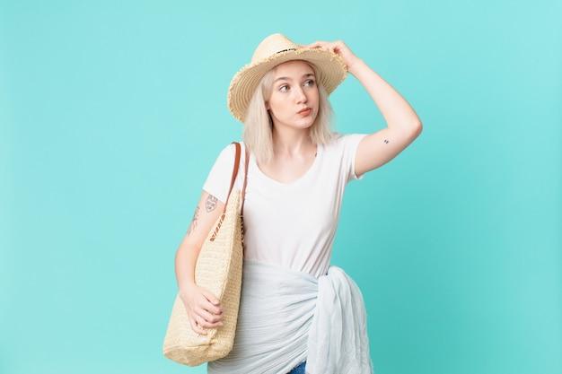 Bella donna bionda che si sente perplessa e confusa, grattandosi la testa. concetto di estate