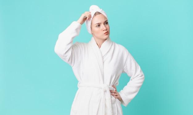 Bella donna bionda che si sente perplessa e confusa, si gratta la testa e indossa l'accappatoio