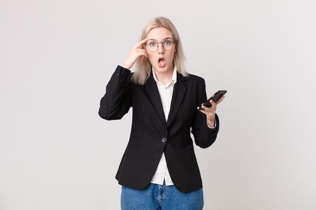 Bella donna bionda che sembra sorpresa, realizzando un nuovo pensiero, idea o concetto e tenendo in mano un telefono cellulare