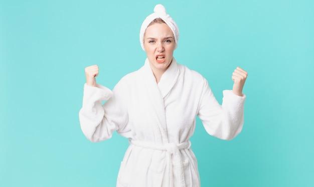 Bella donna bionda che grida in modo aggressivo con un'espressione arrabbiata e indossa un accappatoio