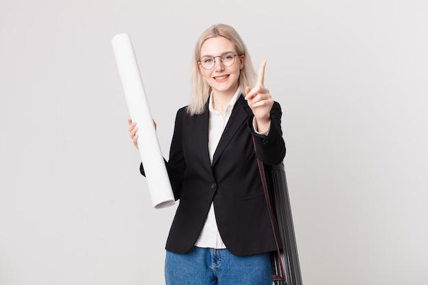 Bella donna bionda che sorride con orgoglio e sicurezza facendo il numero uno. concetto di architetto