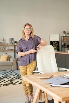 Donna bionda rilassata in abbigliamento casual e pinne utilizza lo smartphone mentre è in piedi da poltrona e tavolo durante il lavoro in ambiente domestico