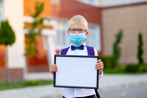 Uno scolaro biondo con gli occhiali e una maschera protettiva si trova a scuola e tiene un cartello con un lenzuolo bianco.