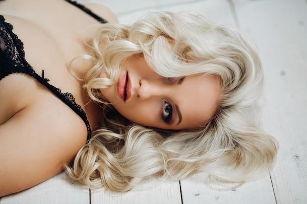 Bella donna bionda sexy con capelli ricci biondi lunghi lussuosi in posa in lingerie nera con pizzo, moda elegante trucco