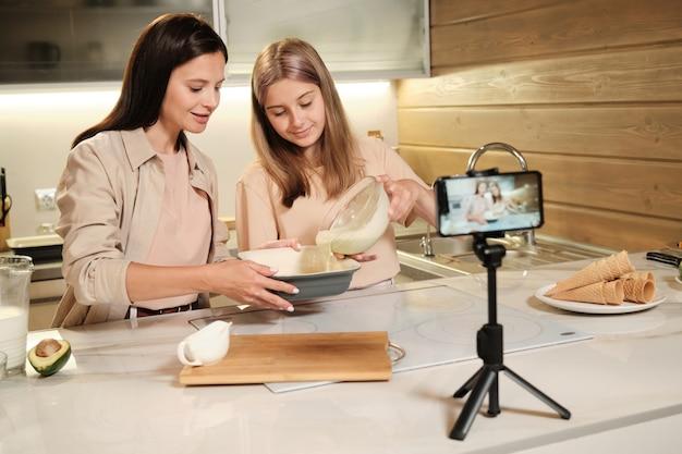 Ragazza adolescente bionda versando la miscela di gelato fatto in casa ingredienti nella grande ciotola davanti alla fotocamera dello smartphone in cucina