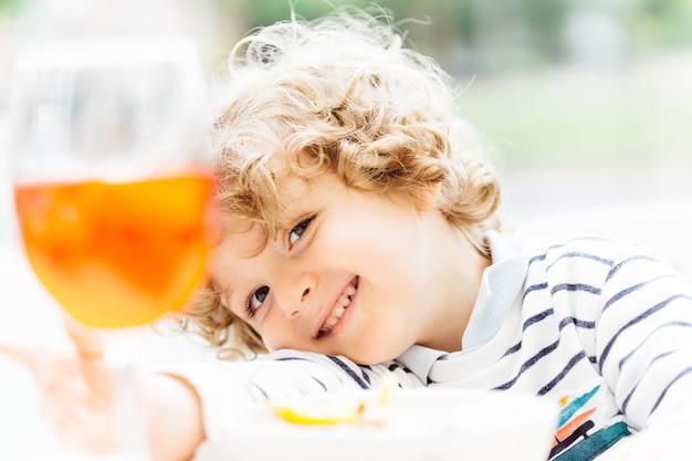 Bambino biondo di tre anni con i riccioli sorridente appoggiato al braccio sulla terrazza di un bar in estate. piani concettuali con i bambini. vacanze in spagna