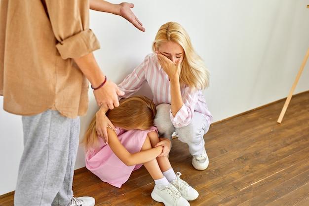 La donna bionda e la ragazza del bambino si siede che soffrono di crudeltà del padre, concetto di relazioni abusive, l'uomo sta urlando e punendo i membri della famiglia