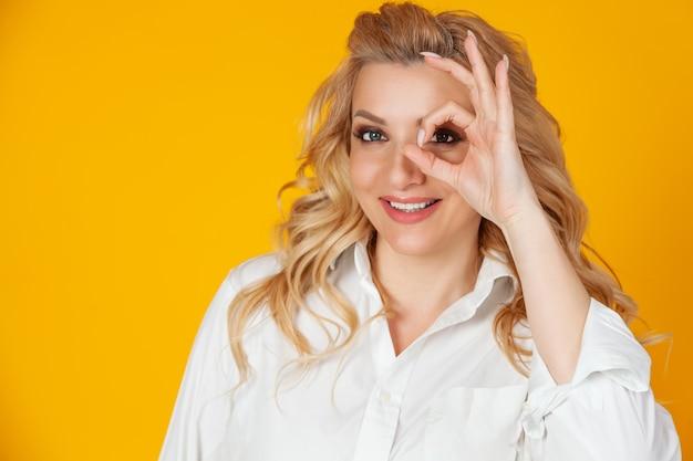 Donna bionda che ritiene ottimista felice che mostra cerchio giusto sopra l'occhio che sorride felicemente. si sente felice ottimista mostrando ok