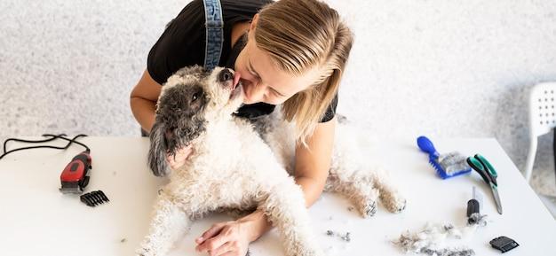 Donna bionda che cura un cane a casa