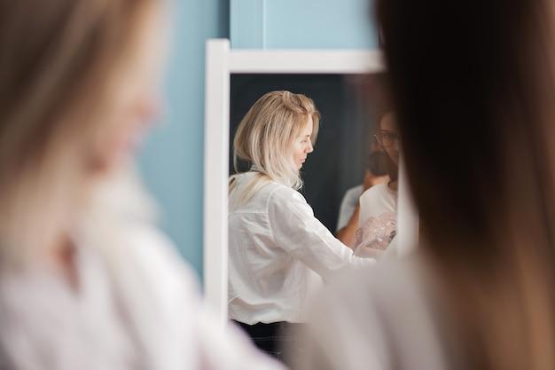 Una donna bionda sorride con una tapeline sul collo laboratorio di sartoria di moda