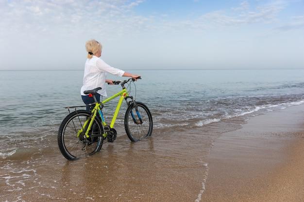 Donna bionda in jeans che camminano nel mare wheeling una bicicletta lungo un litorale sabbioso in una nebbiosa giornata in spiaggia con spazio di copia