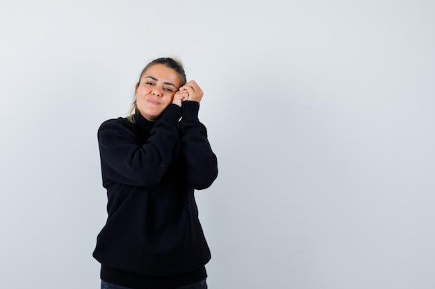 Donna bionda che si appoggia la testa sulle mani in maglione nero e dall'aspetto sognante, vista frontale.