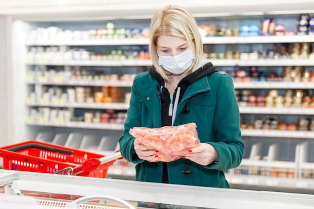 Donna bionda in una mascherina medica sta acquistando in un supermercato nel dipartimento degli alimenti congelati. quarantena durante la pandemia di coronavirus.